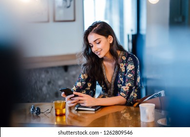 A young Indian Asian student girl is checking her smartphone as she enjoys a cup of coffee in a cafe during the day. She is smiling as she plays with her smartphone.