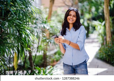 A young Indian Asian teenage girl smiles as she walks down a garden path with her smartphone. She is checking her smartphone.