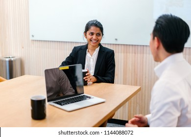 A young Indian Asian woman has a meeting or interview with a Chinese manager in a meeting room during the day. They are professionally dressed and she is smiling genuinely as she speaks.