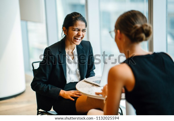 A young Indian Asian woman has a business meeting (interview) with a Caucasian white woman in an office during the day. They are both young, attractive and professionally dressed.