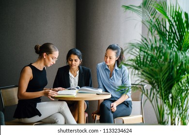 A young Indian Asian woman is having a business meeting with her team in a meeting room. They are looking over a book that they are reading together in the day.