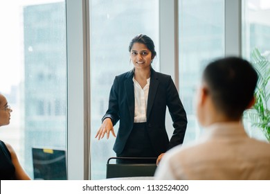 A young Indian Asian woman stands up in front of her diverse team and is leading a meeting, training or presentation in their office during the daytime. They are an ethnically diverse team.