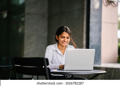 A young Indian Asian woman is typing and working in a laptop in the day (applying for a job, etc). She is wearing a professional, crisp white shirt and she is smiling as she types on her laptop.