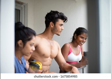 An young Indian Bengali group of friends/siblings are enjoying themselves standing on the balcony after work out in white background. Indian lifestyle.