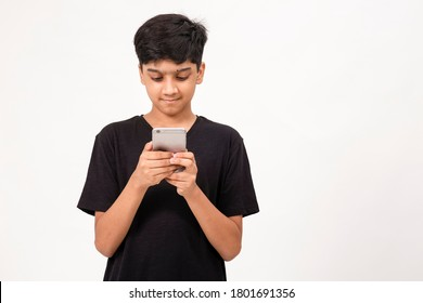 Young Indian boy using mobile phone. Cute teenager checks social media on phone
