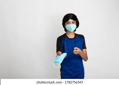Young Indian boy wearing Covid protection mask, boy displays face mask