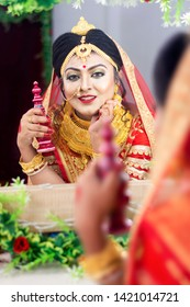 Young Indian bride smiling and looking at mirror with a wooden sindur / sindoor box in her hand