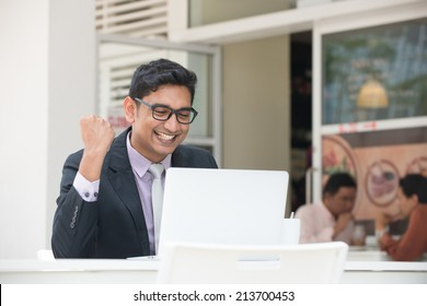 young indian business male on laptop and coffee at a cafe with happy emotion