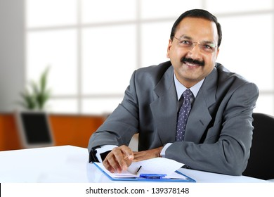 Young Indian business man sitting at his desk