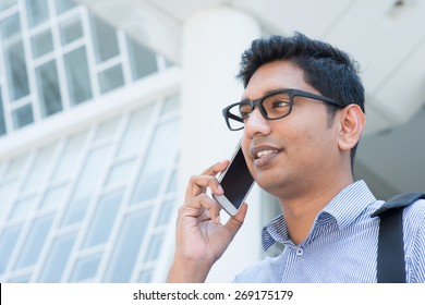 Young Indian business man talking on phone in front modern office building.