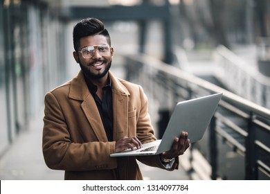 Young indian business man wear in coat and glasses standing outdoor with laptop in front of business building