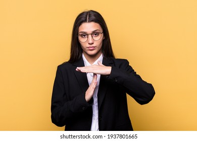 Young Indian business woman isolated on yellow background showing a timeout gesture.
