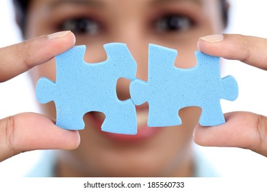 Young Indian business woman joining two jigsaw puzzle pieces against white background