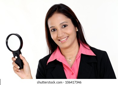 Young Indian business woman with magnifier against white