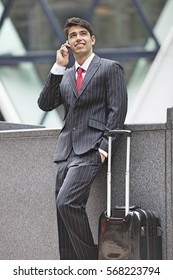 Young Indian businessman communicating on cell phone while standing next to luggage bag