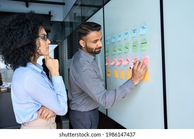 Young indian businessman manager writing strategy ideas on sticky notes on whiteboard and female African American colleague looking at his strategy scrum presentation. Business project planning.