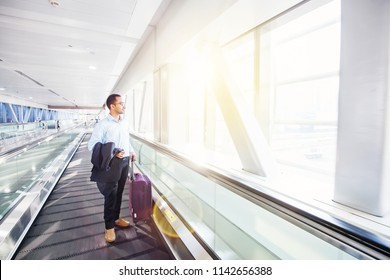Young Indian businessman traveling by travelator in airport terminal