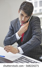 Young Indian businessman using cell phone at office desk