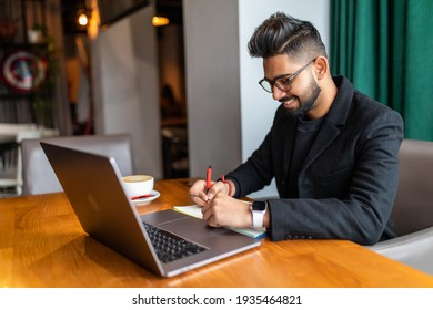 Young Indian businessman using a laptop during office break at cafe, relaxing with a cup of coffee. India male business man, real modern office building as background.