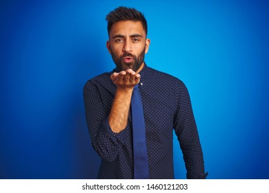 Young indian businessman wearing elegant shirt and tie standing over isolated blue background looking at the camera blowing a kiss with hand on air being lovely and sexy. Love expression.