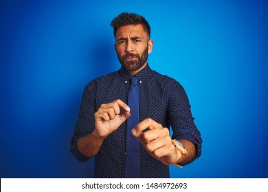 Young indian businessman wearing elegant shirt and tie standing over isolated blue background disgusted expression, displeased and fearful doing disgust face because aversion reaction.