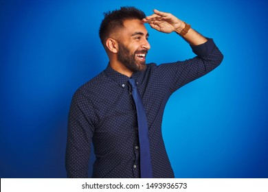Young indian businessman wearing elegant shirt and tie standing over isolated blue background very happy and smiling looking far away with hand over head. Searching concept.