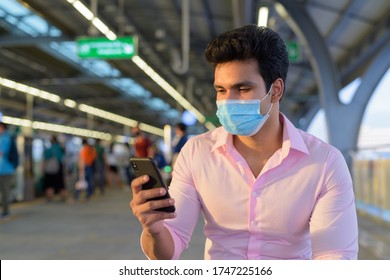 Young Indian businessman wearing mask and sitting with distance while using phone at the skytrain station