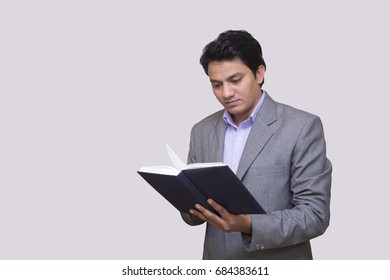 young indian businessmen reading book
