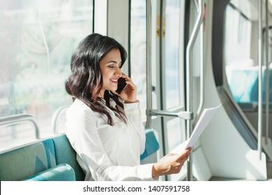 Junge indische Geschäftsfrau liest Dokumente und telefonisch in der Straßenbahn von Dubai
