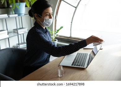 Young indian businesswoman using antiseptic sanitizer, cleaning computer screen monitor before starting working in office. Female employee in breath protective facemask disinfecting workplace.