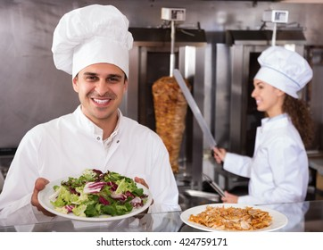 Young indian chef offering tasty kebab at counter and smiling