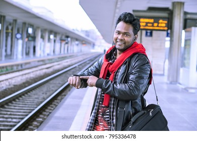 Young indian commuter waiting at train station - Casual asian man standing on platforms pointing finger at wrist watch looking at camera smiling - Concep of everyday life and public transport service