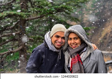 Young Indian couple enjoying their first snowfall during winter holidays in Kufri, Shimla, Himachal Pradesh. It is a popular winter getaway where people come to enjoy snowfall, skiing & winter sports