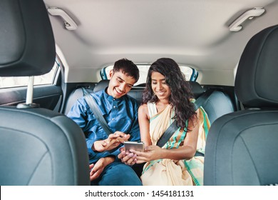 Young Indian couple wearing traditional ethnic clothes using mobile phone on a back seat of a car
