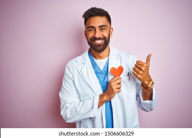 Young indian doctor man holding paper heart standing over isolated pink background happy with big smile doing ok sign, thumb up with fingers, excellent sign