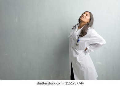 Young indian doctor woman against a wall with back pain due to work stress, tired and astute