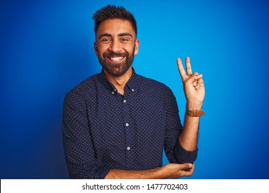 Young indian elegant man wearing shirt standing over isolated blue background smiling with happy face winking at the camera doing victory sign. Number two.