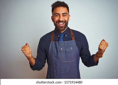 Young indian employee man wearing apron uniform standing over isolated white background celebrating surprised and amazed for success with arms raised and open eyes. Winner concept.