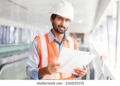 Young indian engineer holding contract