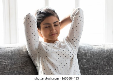 Young indian ethnicity woman resting seated on couch at home near window sunny light through glass, serene tranquil girl closed eyes put hands behind head enjoy repose relaxation and fresh air concept