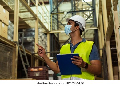 Young Indian factory warehouse worker wearing a protective face mask and safety helmet while working in logistic industry indoor. 30s man checking stock order during Coronavirus Covid 19 pandemic