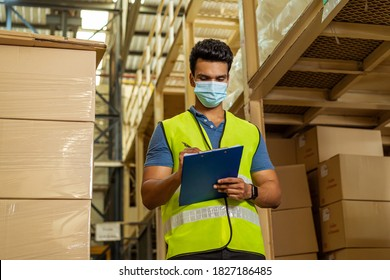 Young Indian factory warehouse worker wearing a protective face mask while working in logistic industry indoor. 30s man checking item stock order during Coronavirus Covid 19 pandemic outbreak