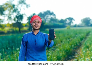 Young indian farmer showing smartphone screen at agriculture field
