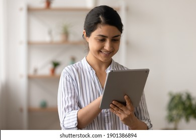 Young indian female in good mood stand at living room with tablet pc device corresponding with friend at social network. Confident smiling mixed race lady check mail client on pad using wifi internet