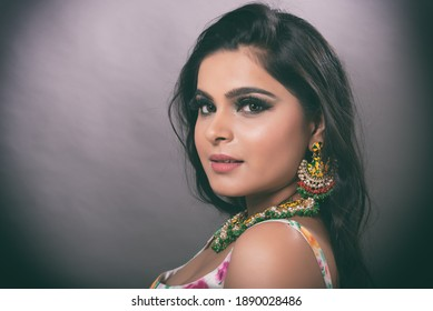 Young Indian female wearing ethnic green floral summer dress with jewelry and makeup