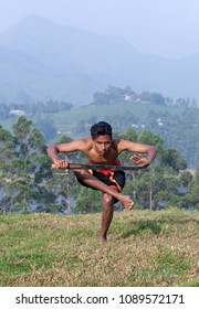 Young Indian fighter balancing with sword during Kalaripayattu marital art demonstration in Kerala, South India