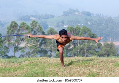 Young Indian fighter doing exercises with sword during Kalaripayattu marital art demonstration in Kerala, South India
