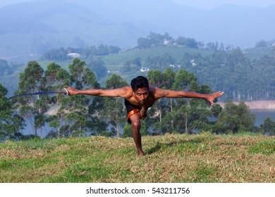 Young Indian fighter performing Kalaripayattu marital art demonstration in Kerala, South India