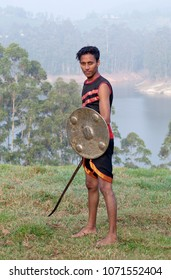 Young Indian fighter with sword and shield poses for a photo during Kalaripayattu marital art demonstration in Kerala, South India