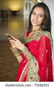 Young Indian girl in traditional clothing using a cellphone.